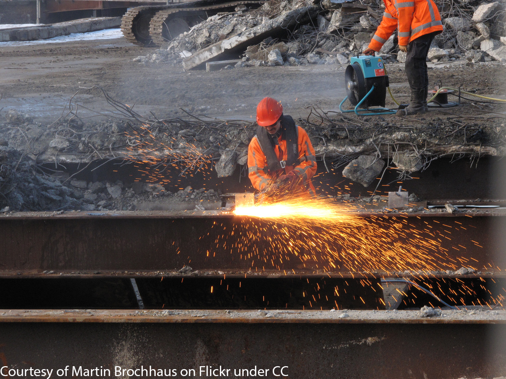 A construction worker cutting steel
